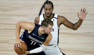 Los Angeles Clippers' Kawhi Leonard, right, applies pressure on Dallas Mavericks' Luka Doncic (77) during the second half of an NBA basketball game Thursday, Aug. 6, 2020 in Lake Buena Vista, Fla. (AP Photo/Ashley Landis, Pool)