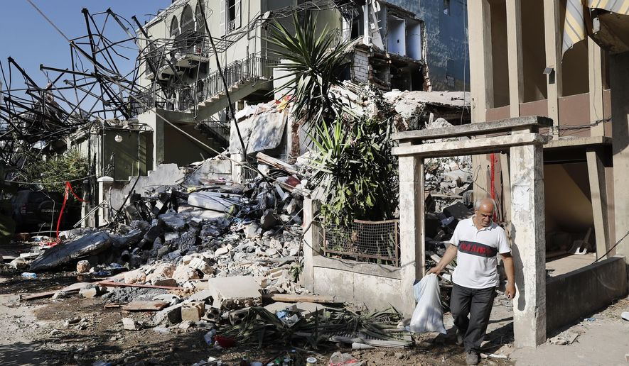 A Lebanese man carries his belongings as he leaves his destroyed house near the scene where an explosion hit on Tuesday the seaport of Beirut, Lebanon, Thursday, Aug. 6, 2020. Lebanese army bulldozers plowed through wreckage to reopen roads around Beirut's demolished port on Thursday as the government pledged to investigate the devastating explosion and placed port officials under house arrest. (AP Photo/Hussein Malla)
