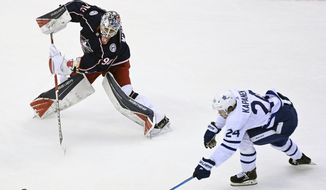 Columbus Blue Jackets goaltender Elvis Merzlikins (90) comes far out of his net to play the puck as Toronto Maple Leafs right wing Kasperi Kapanen (24) chases during the second period of an NHL hockey playoff game  Thursday, Aug. 6, 2020, in Toronto. (Nathan Denette/The Canadian Press via AP)