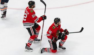 Chicago Blackhawks' Ryan Carpenter (22) and Matthew Highmore (36) celebrate a goal against the Edmonton Oilers during the third period of an NHL hockey playoff game Wednesday, Aug. 5, 2020, in Edmonton, Alberta. (Codie McLachlan/The Canadian Press via AP)