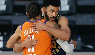 Indiana Pacers' Naz Mitrou-Long, rear, and Phoenix Suns' Ricky Rubio (11) hug at the end of an NBA basketball game Thursday, Aug. 6, 2020, in Lake Buena Vista, Fla. (Kevin C. Cox/Pool Photo via AP)