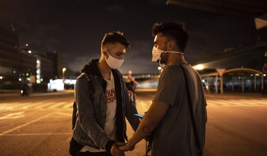 Piotr Grabarczyk and his boyfriend Kamil Pawlik, right, from Poland, wait for a taxi outside the airport after Grabarczyk arrived in Barcelona, Spain, early Wednesday, July 29, 2020. Like them, many LGBT people are choosing to leave Poland amid rising homophobia promoted by President Andrzej Duda and other right-wing populist politicians in power. (AP Photo/Felipe Dana)