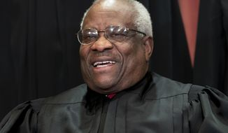 In this Nov. 30, 2018, file photo, Supreme Court Associate Justice Clarence Thomas, appointed by President George H. W. Bush, sits with fellow Supreme Court justices for a group portrait at the Supreme Court Building in Washington. Thomas has never been afraid to turn right when his colleagues turn left, or in any direction really as long as there's a place to plug in his 40-foot refitted tour bus. (AP Photo/J. Scott Applewhite, File)
