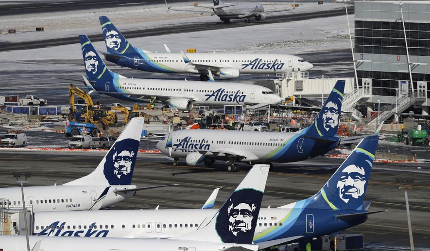 In this Feb. 5, 2019, file photo, Alaska Airlines planes are parked at a gate area at Seattle-Tacoma International Airport in Seattle. Alaska Airlines said more than 300 employees among the company's workforce in Anchorage may lose their jobs on Oct. 1, 2020. The company said the Anchorage layoffs are part of company-wide job cuts because of the economic fallout from the coronavirus pandemic, Alaska Public Media reported Tuesday, Aug. 4. (AP Photo/Ted S. Warren, File)