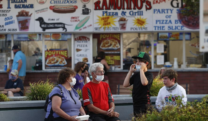 Visitors wear masks to help prevent the spread of the coronavirus, Wednesday, Aug. 5, 2020, at Old Orchard Beach, Maine. Tourists have returned to the popular seaside town in a state that ranks one of the lowest in the nation in positive cases of coronavirus. (AP Photo/Robert F. Bukaty)