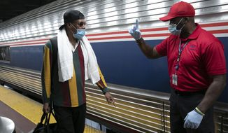 A traveler arriving on a train that originated in Miami gets directions from a porter, right, at Amtrak's Penn Station, Thursday, Aug. 6, 2020, in New York. Mayor Bill de Blasio is asking travelers from 34 states, including Florida where COVID-19 infection rates are high, to quarantine for 14 days after arriving in the city. (AP Photo/Mark Lennihan)