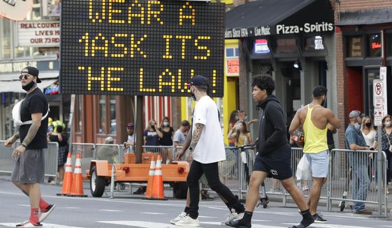A sign encouraging the wearing of masks stands in downtown Nashville, Tenn., Wednesday, Aug. 5, 2020. The wearing of face coverings is required in most public indoor and outdoor situations in Nashville due to an increase of COVID-19 cases. (AP Photo/Mark Humphrey)
