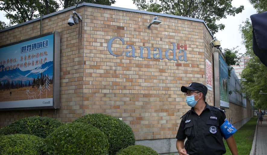 A security officer wearing a face mask to protect against the coronavirus stands outside the Canadian Embassy in Beijing, Thursday, Aug. 6, 2020. China announced on Friday that it had sentenced a Canadian to death on drug charges, the second day in a row Chinese courts handed down the death penalty to a Canadian citizen. (AP Photo/Mark Schiefelbein)