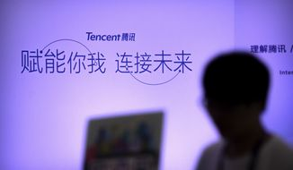 In this April 27, 2017, photo, an attendee walks past a booth for Chinese technology firm Tencent, makers of the messaging app WeChat, at the Global Mobile Internet Conference (GMIC) in Beijing. President Donald Trump on Thursday, Aug. 6, 2020, ordered a sweeping but unspecified ban on dealings with the Chinese owners of consumer apps TikTok and WeChat, although it remains unclear if he has the legal authority to actually ban the apps from the U.S. (AP Photo/Mark Schiefelbein)