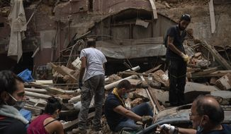 People remove debris from a house damaged by Tuesday's explosion in the seaport of Beirut, Lebanon, Friday, Aug. 7, 2020. Rescue teams were still searching the rubble of Beirut's port for bodies on Friday, nearly three days after a massive explosion sent a wave of destruction through Lebanon's capital, killing over a hundred people and wounding thousands. (AP Photo/Felipe Dana)