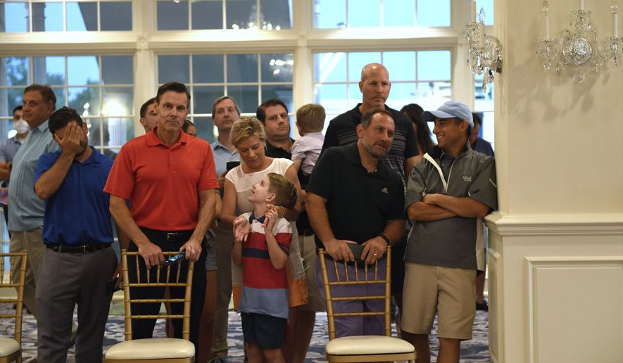 People stand behind chairs as they wait to watch President Donald Trump speak at Trump National Golf Club Bedminster in Bedminster, N.J., Friday, Aug. 7, 2020. (AP Photo/Susan Walsh)