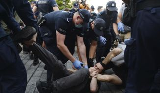 Police scuffle with pro-LGBT protesters angry at the arrest of an LGBT activist in Warsaw, Poland on Friday, Aug. 7, 2020. The incident comes amid rising tensions in Poland between LGBT activists and a conservative government that is opposed to LGBT rights. (AP Photo/Czarek Sokolowski)