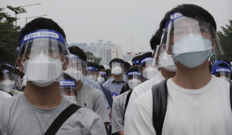 Interns and resident doctors attend a rally against the government medical policy in Seoul, South Korea, Friday, Aug. 7, 2020. Thousands of young doctors in South Korea began a strike Friday in protest of government medical policy, causing concerns about treatment of patients amid the coronavirus pandemic. (AP Photo/Ahn Young-joon)