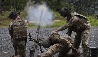 Cadets learn to fire mortars, Friday, Aug. 7, 2020, at the U.S. Military Academy in West Point, N.Y. The pandemic is not stopping summer training. Cadets had to wear masks this year for much of the training. (AP Photo/Mark Lennihan)