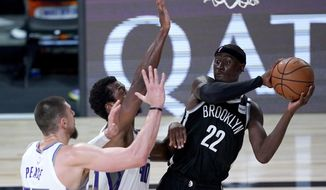 Brooklyn Nets' Caris LeVert (22) looks to pass the ball as Sacramento Kings' Alex Len, left, and Harrison Barnes defend during the second half of an NBA basketball game Friday, Aug. 7, 2020 in Lake Buena Vista, Fla. (AP Photo/Ashley Landis, Pool)