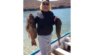 This undated photo provided by Azalia Sandoval, taken in Guaymas Bay, Mexico, shows Carlos Manuel Sandoval showing off the two fish he caught that day. Sandoval was born in Guaymas on Feb. 13, 1955, and he continued to hear the siren call of the sea more than a quarter-century after he and his family moved to Phoenix. He still traveled back to his hometown port and other coastal communities on Mexico's Sea of Cortez at least annually to indulge his passion for fishing. Sandoval died June 30 from complications of COVID-19 at age 65. (Courtesy of Azalia Sandoval via AP)