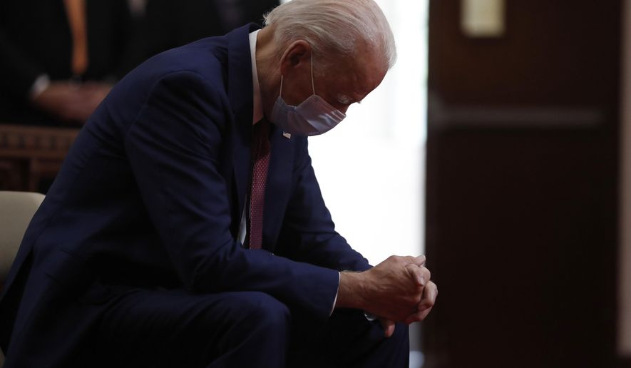 """In this  June 1, 2020, file photo, Democratic presidential candidate, former Vice President Joe Biden bows his head in prayer as he visits Bethel AME Church in Wilmington, Del. Photos in a campaign ad for President Donald Trump show that former Vice President Biden is """"alone, hiding, diminished."""" The ad blurs details that show Biden is praying in a church. The ad was tweeted by @TeamTrump on Wednesday, Aug. 5, 2020. (AP Photo/Andrew Harnik, File)"""