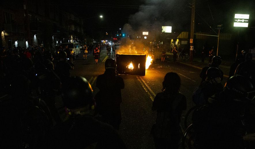 A waste receptacle is set on fire near the Portland Police Association building during a protest in Portland, Ore., on Tuesday, Aug. 4, 2020.  A riot was declared early Wednesday during demonstrations in Portland after authorities said people set fires and barricaded public roadways.(Dave Killen /The Oregonian via AP) **FILE**