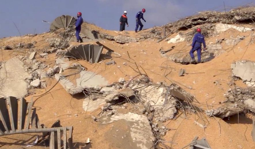 In this photo taken from footage provided by the Russian Emergency Situations Ministry press service, Russian Emergency Situations personnel walk on the site of the explosion in the port of Beirut, Lebanon, on Thursday, Aug. 6, 2020. Russia's emergency officials say the country sent five planeloads of aid to Beirut after an explosion in the Lebanese capital's port killed at least 100 people and injured thousands on Tuesday. Russia's Ministry for Emergency Situations sent rescuers, medical workers, a makeshift hospital and a lab for coronavirus testing to Lebanon. (AP Photo/Ministry of Emergency Situations press service via AP)