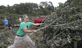 August Riedinger pulls a pile of brush off his trailer at the transfer station in Southington, Conn., Thursday, Aug. 6, 2020.  Residents unloaded tree limbs and other debris caused by Tropical Storm Isais. (Dave Zajac/Record-Journal via AP)