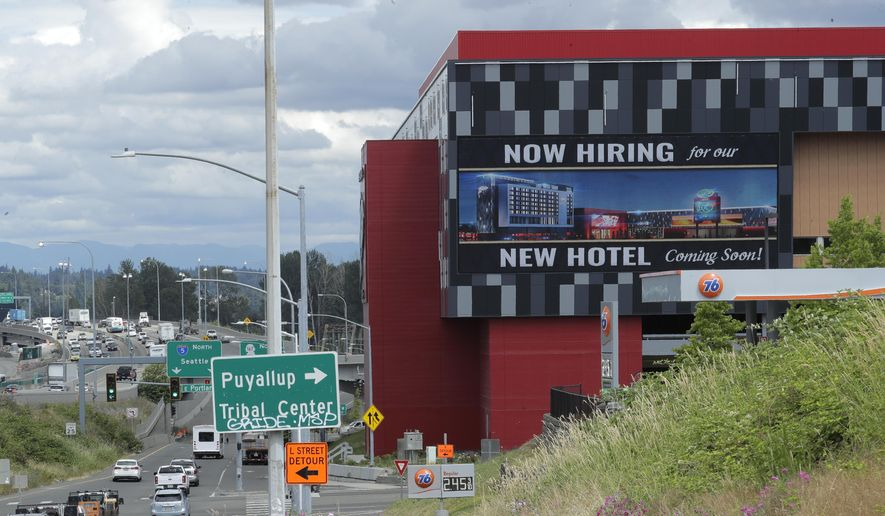 "In this July 9, 2020, file photo, a large video display reads ""Now hiring for our new hotel coming soon!,"" at the new Emerald Queen Casino, which is open, and owned by the Puyallup Tribe of Indians, in Tacoma, Wash. (AP Photo/Ted S. Warren, File)"