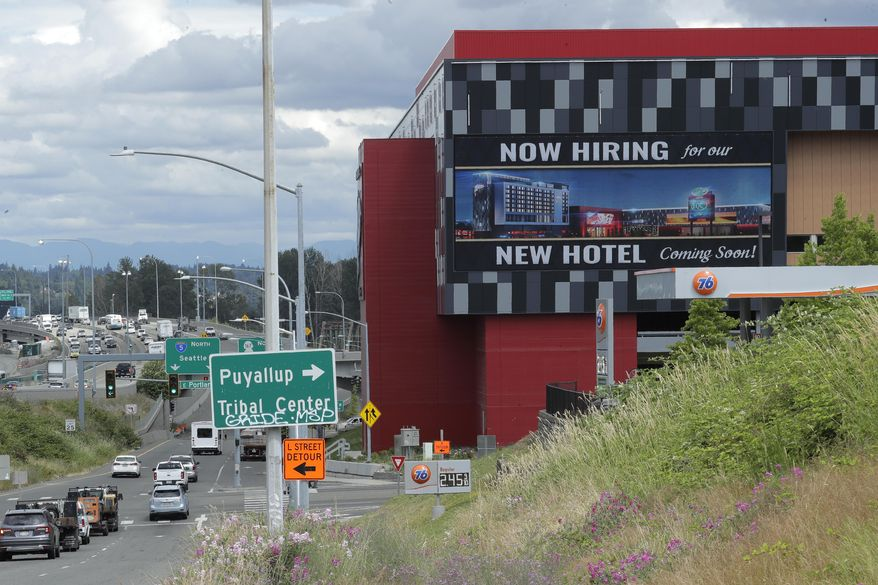 """In this July 9, 2020, file photo, a large video display reads """"Now hiring for our new hotel coming soon!,"""" at the new Emerald Queen Casino, which is open, and owned by the Puyallup Tribe of Indians, in Tacoma, Wash. (AP Photo/Ted S. Warren, File)"""