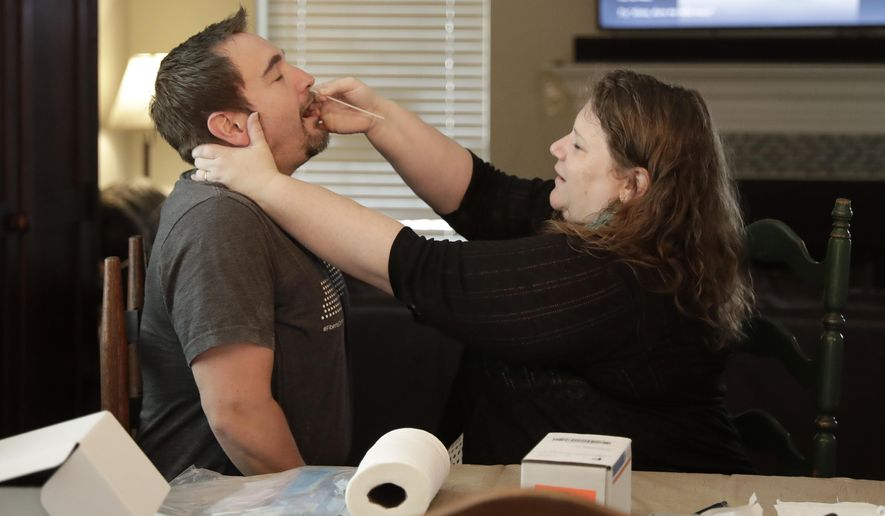 Mendy McNulty swabs the nose of her husband, Joe, in their home in Mount Juliet, Tenn., Tuesday, July 28, 2020. The family is participating in testing done twice a month to help answer some of the most vexing questions about the coronavirus. (AP Photo/Mark Humphrey) **FILE**