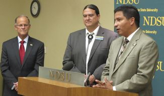 """FILE - In this June 18, 2014, file photo, North Dakota Indian Affairs Commissioner Scott Davis, right, speaks at North Dakota State University in Fargo, N.D. Davis says the state's tribes are """"back to square one"""" after recent coronavirus outbreaks linked to July 4th events. The primary counties where the state's five federally recognized tribes are located are all ranked in the top 20 for the number of virus cases per capita in the last two weeks. Davis says tribal leaders are taking the virus seriously and that he has warned the pandemic will probably last a long time. (AP Photo/Dave Kolpack, File)"""
