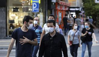 People wearing face masks to protect against the spread of coronavirus, walk in Ankara, Turkey, Thursday, Aug. 6, 2020. Turkey's interior ministry announced new measures Wednesday to curb the spread of COVID-19 as daily confirmed cases peaked above 1,000. (AP Photo/Burhan Ozbilici)