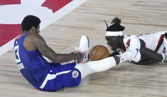 Los Angeles Clippers guard Paul George (13), left, and Portland Trail Blazers forward Wenyen Gabriel (35) battle for a loose ball during the first half of an NBA basketball game Saturday, Aug. 8, 2020, in Lake Buena Vista, Fla. (Kim Klement/Pool Photo via AP)