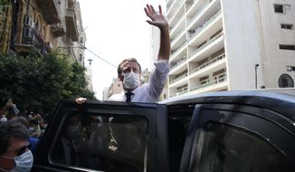 French President Emmanuel Macron waves as he visits Beirut, Lebanon, Thursday Aug.6, 2020. French President Emmanuel Macron has arrived in Beirut to offer French support to Lebanon after the deadly port blast.(AP Photo/Thibault Camus, Pool)