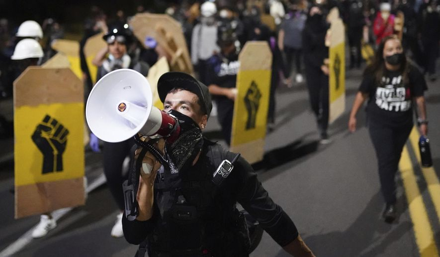 A protester leads a crowd of demonstrators toward the Multnomah County Sheriff's Office on Friday, Aug. 7, 2020 in Portland, Ore. (AP Photo/Nathan Howard)