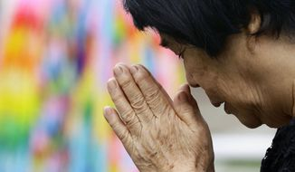 A bereaved family member prays for the victims of U.S. atomic bombing at the Atomic Bomb Hypocenter Park in Nagasaki, southern Japan, Sunday, Aug. 9, 2020. Nagasaki marked the 75th anniversary of the atomic bombing on Sunday. (Kyodo News via AP)