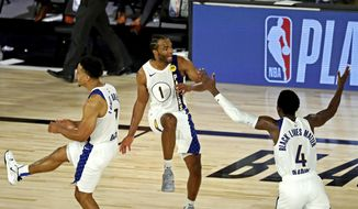 Indiana Pacers forward T.J. Warren (1) celebrates with guards Malcolm Brogdon (7) and Victor Oladipo (4) after a play against the Los Angeles Lakers during an NBA basketball game Saturday, Aug. 8, 2020, in Lake Buena Vista, Fla. (Kim Klement/Pool Photo via AP)  **FILE**