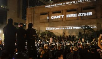 "FILE - In this Saturday, July 25, 2020, file photo, the words ""I can't breathe"" are flashed on a wall during a Black Lives Matter protest in Portland, Ore. State legislatures across the U.S. are pushing an array of policing reforms after the demonstrations related to the death of George Floyd last spring, from banning chokeholds to making it easier to hold officers legally accountable for their actions. (AP Photo/Marcio Jose Sanchez, File)"