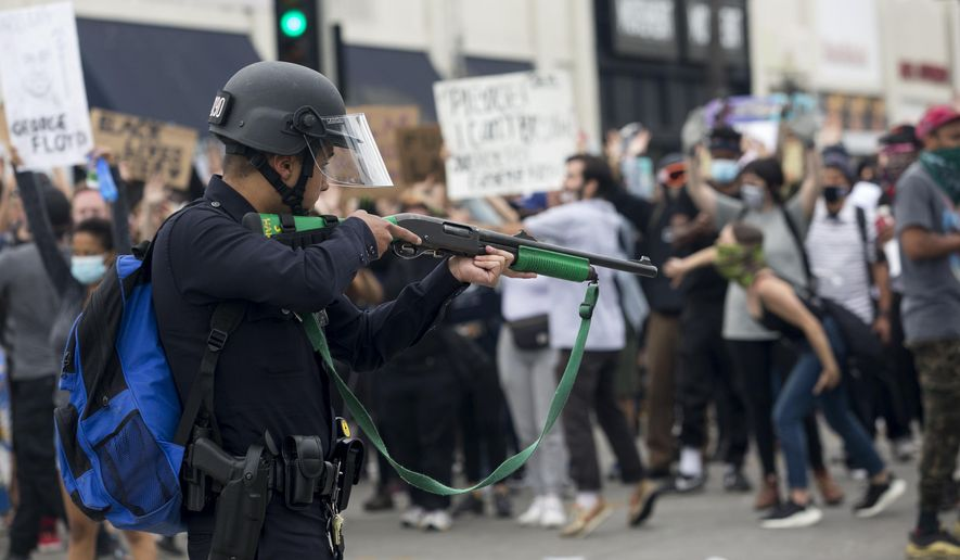 FILE - In this May 30, 2020, file photo, a police officer prepares to fire rubber bullets during a protest over the death of George Floyd in Los Angeles. California lawmakers are pushing to enact nearly a dozen policing reform laws driven by nationwide outrage and protests after  Floyd's death in May.  (AP Photo/Ringo H.W. Chiu, File)
