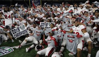 FILE - In this Dec. 7, 2019, file photo, members of the Miami of Ohio team pose on the field after the Mid-American Conference championship NCAA college football game against Central Michigan, in Detroit. The Mid-American Conference on Saturday, Aug. 8, 2020, became the first league competing at college football's highest level to cancel its fall season because of COVID-19 concerns. A person with knowledge of the decision told The Associated Press the university president's voted to not play in the fall and consider a spring season. The person spoke to AP on condition of anonymity because an official announcement was still being prepared.(AP Photo/Carlos Osorio, File)