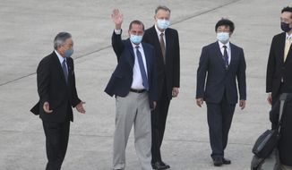 U.S. Health and Human Services Secretary Alex Azar, second left, waves to media as he arrives at Taipei Songshan Airport in Taipei, Taiwan, Sunday, Aug. 9, 2020. Azar arrived in Taiwan on Sunday in the highest-level visit by an American Cabinet official since the break in formal diplomatic relations between Washington and Taipei in 1979. (AP Photo/Chiang Ying-ying)