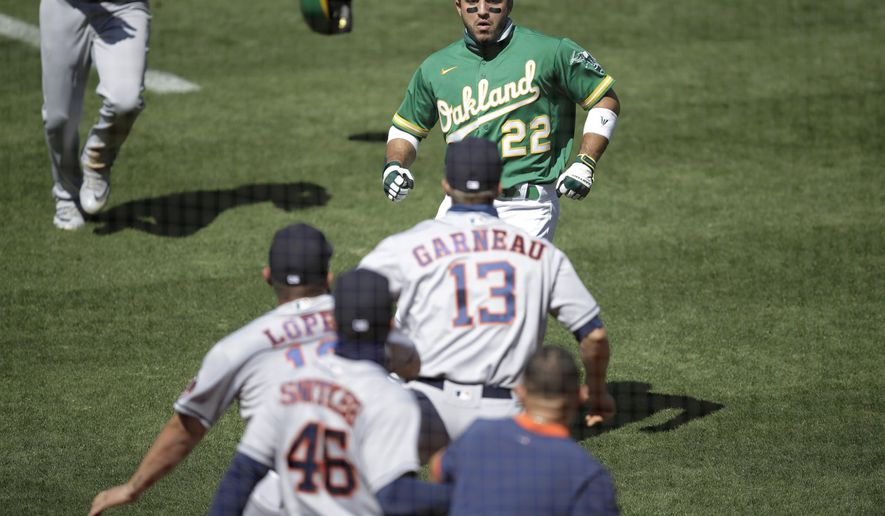 Oakland Athletics' Ramon Laureano (22) charges the Houston Astros' dugout after being hit by a pitch thrown by Humberto Castellanos during the seventh inning of a baseball game Sunday, Aug. 9, 2020, in Oakland, Calif. (AP Photo/Ben Margot)