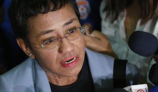 FILE - Maria Ressa, the award-winning head of a Philippine online news site Rappler, talks to the media after posting bail at a Regional Trial Court following an overnight arrest by National Bureau of Investigation agents on a libel case in Manila, Philippines on Feb. 14, 2019. A new documentary tracks Ressa's dual life in recent years. She's seen smiling while accepting international honors and praise from the likes of George Clooney, then grimly facing down online harassment, legal action and real world threats for her news site's reporting on the drug war waged by President Rodrigo Duterte. (AP Photo/Bullit Marquez, File)