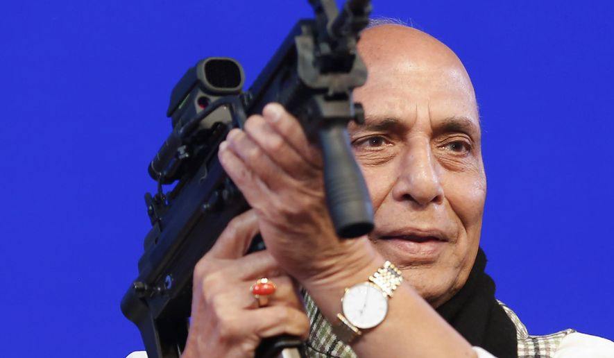 FILE- In this Feb. 7, 2020 file photo,  Indian Defense Minister Rajnath Singh holds a model of a light machine gun during DefExpo20 in Lucknow, India. India will ban the imports of 101 items of military equipment in an effort to boost indigenous production and improve self-reliance in weapons manufacturing, Singh said Sunday. (AP Photo/Rajesh Kumar Singh, File)