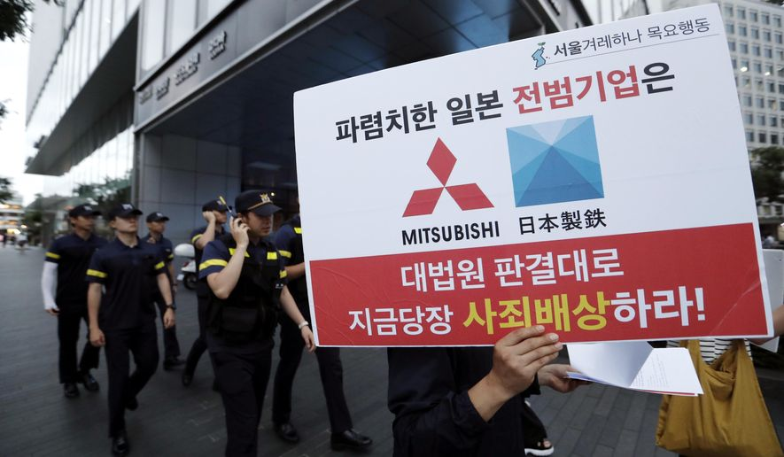 """FILE - In this July 11, 2019, file photo, a protester with a banner walks to attend a rally denouncing the Japanese government's decision on their exports to South Korea in front of the Japanese Embassy in Seoul, South Korea. The modern legacy of a dark chapter in Japan's history, when hundreds of thousands of people were brought from the Korean Peninsula and other Asian nations to work in logging, in mines, on farms and in factories as forced labor, lives on in the companies that came to dominate the Japanese economy after World War II. Many of those companies are still facing demands for compensation that they say were settled by treaty decades ago. The sign reads """"The shameless Japanese company should immediately compensate for its war crimes in accordance with the Supreme Court ruling."""" (AP Photo/Ahn Young-joon, File)"""