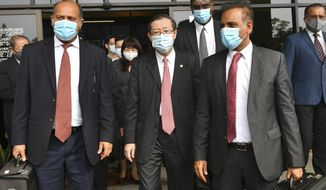Malaysian former Finance Minister and Penang Chief Minister Lim Guan Eng, center, leaves courthouse in Butterworth, Malaysia, Monday, Aug. 10, 2020. Lim pleaded not guilty to a second graft charge relating to a $1.5 billion undersea tunnel project. Lim has slammed the charges as political persecution by the new government. (AP Photo/Gary Chuah)