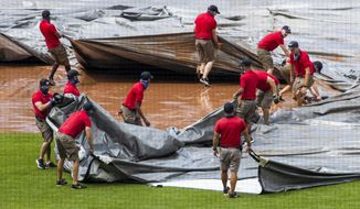 Grounds crew tries to untangle the tarp as they attempt to cover the baseball diamond from a heavy downpour delaying the baseball game during the sixth inning of a baseball game between the Washington Nationals and the Baltimore Orioles in Washington, Sunday, Aug. 9, 2020. (AP Photo/Manuel Balce Ceneta)