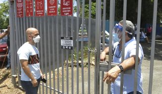 An electoral official, right, tells a voter that the ballots haven't arrived at a voting center in Carolina, Puerto Rico, Sunday, Aug. 9, 2020. Puerto Rico's primaries were marred on Sunday by a lack of ballots in a majority of centers across the U.S. territory, forcing frustrated voters who braved a spike in COVID-19 cases to turn around and go back home. (AP Photo/Danica Coto)