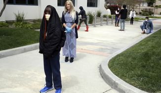 """FILE - In this Sunday, April 5, 2020, file photo, worshipers line up to take communion on Palm Sunday outside of Godspeak Calvary Chapel in Newbury Park, Calif. The pastor of a California church has vowed to continue holding indoor worship in defiance of coronavirus health orders after a judge issued a temporary restraining order barring the church from doing so. Ventura County Superior Court Judge Matthew Guasco cited """"an immediate threat to public health and safety due to the 2019 novel coronavirus"""" in issuing the temporary restraining order. The order will be in place until another hearing is held on Aug. 21. (AP Photo/Marcio Jose Sanchez, File)"""