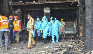Rescuers in protective suits carry the body of a victim from Hotel Swarna Palace where a fire broke out early morning in Vijayawada, Andhra Pradesh state, India, Sunday, Aug. 9, 2020. The fire in the hotel being used as a COVID-19 facility killed seven coronavirus patients. (AP Photo)