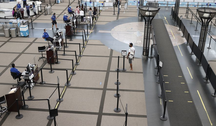 A lone traveler heads to the north security checkpoint in the main terminal of Denver International Airport Wednesday, July 22, 2020, in Denver. (AP Photo/David Zalubowski)