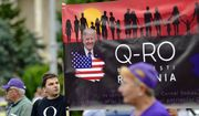 Romanian supporters of QAnon take part in a rally against the government's measures to prevent the spread of COVID-19 infections, like wearing a face mask, in Bucharest, Romania, Monday, Aug. 10, 2020. QAnon is a U.S. conspiracy theory popular among some Trump supporters. (AP Photo/Andreea Alexandru)