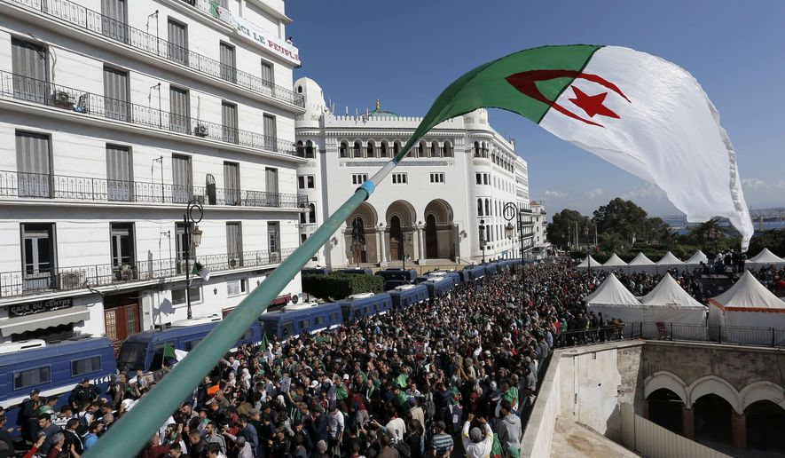 FILE - In this Nov.1, 2019 file photo, Algerian demonstrators take to the streets in the capital Algiers to protest against the government. An Algerian journalist who played a prominent role in covering last year's pro-democracy movement was sentenced Monday to three years in prison, accused of inciting unauthorized demonstrations and attacking national unity. (AP Photo/Toufik Doudou, File)